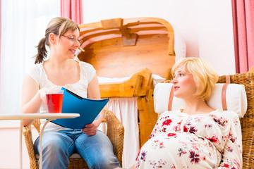 Hebamme mit Mutter bei Schwangerschaftsberatung