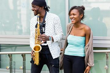 Afrikanisches Paar spielt Saxophon auf Straße