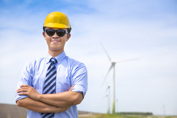 confident  young engineer standing with wind generator