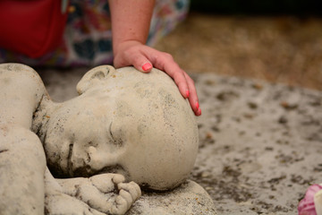 Baby loss mum's hand on statue