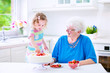 Grandmother baking cake with little granddaughter