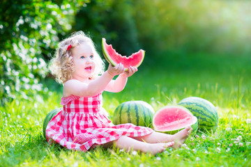 Little nice girl eating watermelon