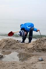 Kind spielt im Winter am Meer