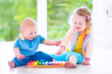 Happy kids playing music with xylophone