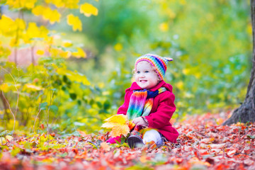 Little funny girl having fun in an autumn sunny park