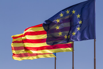 Flags of European Union and Catalonia waving together on a blue