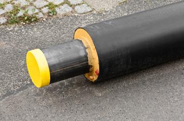 Ein neues Fernwärmerohr liegt auf einer Strasse