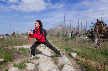Frau bei Dehnübung in toter Baumlandschaft