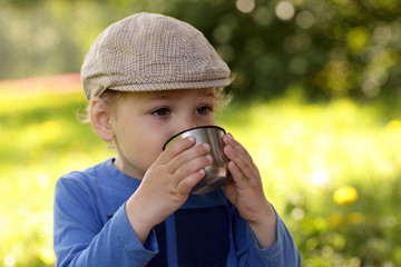 Child drinking tea outdoor