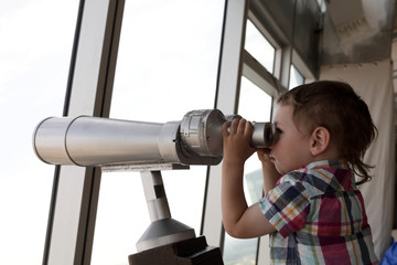 Child looking through pay binoculars