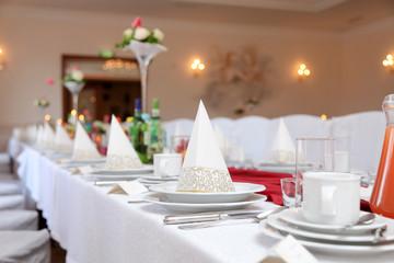 Stół weselny w restauracji z talerzami, filiżankami i sztućcami.