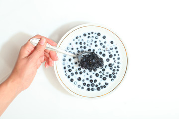 blueberries in a bowl with milk. berries stirred with a spoon