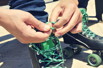 young man tying his roller skates, with a filter effect