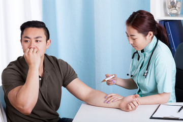 Asian nurse giving vaccination injection to patient