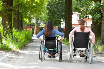 Two women on wheelchairs in park