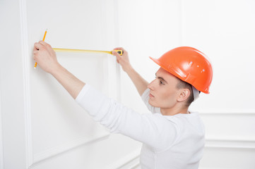 Young handsome worker in helmet with measuring tape
