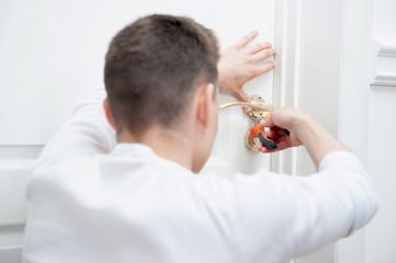 Young man fixing the door handle
