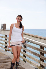 Woman with a fishing pole on a pier
