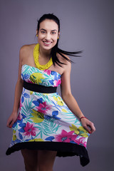 Young Smiling Female Brunette in Sleeveless Hawaii Flower Dress