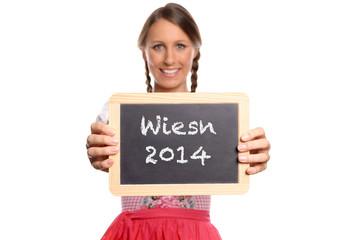 Junge Frau in einem Dirndl hält eine Tafel mit Text