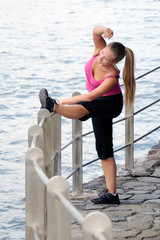 Woman in sportswear outdoors stretching her legs before running