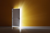 Rays of light through the open white door on orange wall