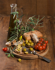Olive bread with olive oil and  cherry tomatoes on old wooden ta