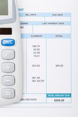 Calculator next to a bill - studio shot