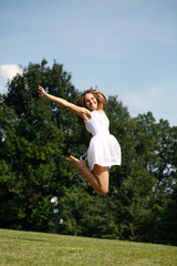 Happy young woman jumping in white dress
