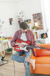 young man sit on a sofa is playing guitar