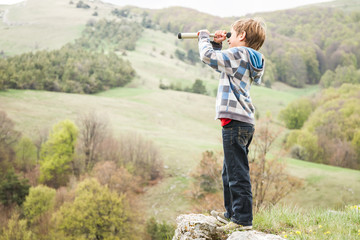 young child boy looking through binocular to the country side
