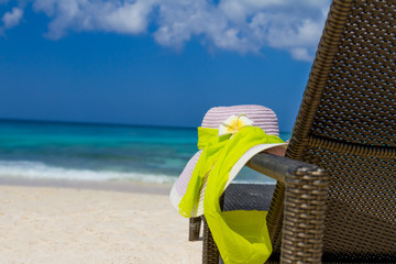 summer hat on beach chair, tropical vacation concept