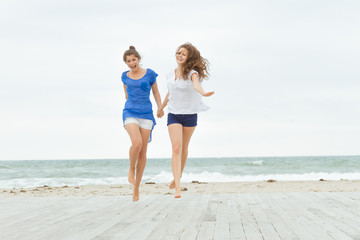 two young happy women enjoying life outdoors isolated over white