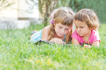 two young happy kids, children reading books on natural backgrou