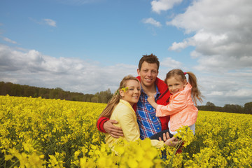 happy family outdoor in rape field