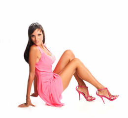 Beautiful dark haired model in pink dress siiting on floor