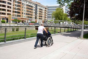 mujer empujando una silla de ruedas por la calle
