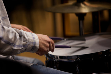 Hands of the man playing a drum set in dark colors