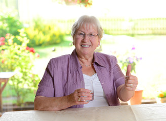 elderly woman with water glass and thumb up