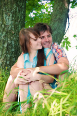 Smiling couple resting near a tree