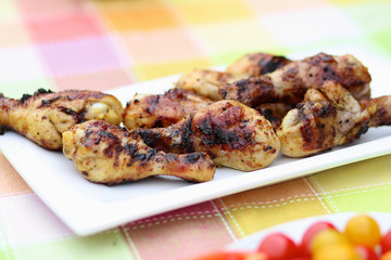 Delicious grilled chicken legs on white plate