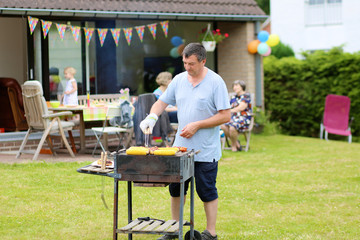 Happy man preparing meat on grill for family party