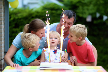 Big family celebrating with cake birthday of 2 years old girl