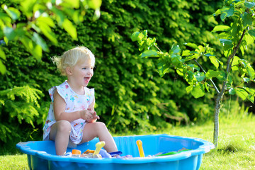 Happy little girl playing in sandbox in the garden on summer day