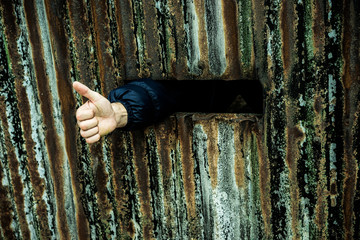 Thumb up shown by a person captive in prison
