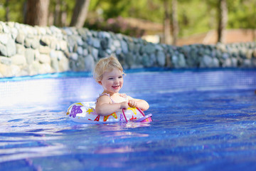Happy little girl swimming in the pool with inflatable ring