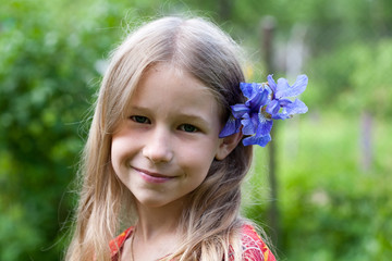 small girl with blue iris flower in her hair