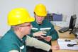 Industrial workers in control room, teamwork