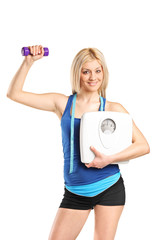 Athletic woman holding a dumbbell and weight scale