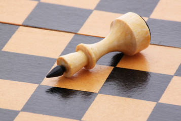 white queen lying on chessboard